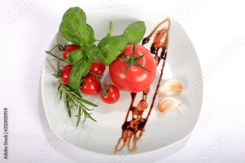 Fototapeta Pomidor czerwony, malinowy i koktajlowy, bazylia, rozmaryn i czosnek na talerzu. obraz