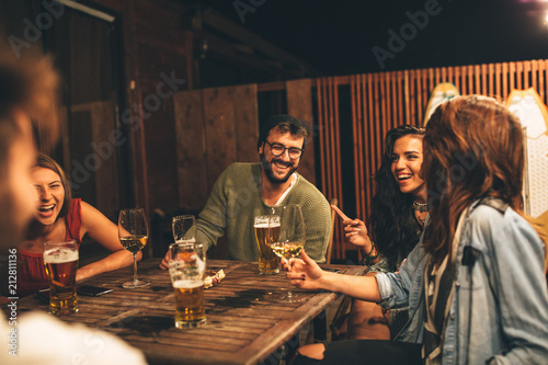 Obraz Group of friends drink beer on the terrace during summer night - fototapety do salonu