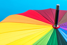 Multi-colored Colorful Umbrella With All Colors Of The Rainbow On A Blue Background. Bright Texture Background.