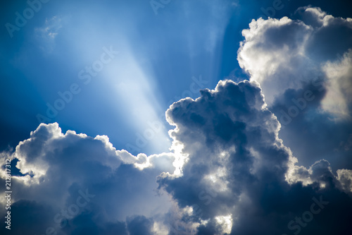 Abstract view of puffy summer thunderstorm clouds backlit by sun with rays streaming through Canvas Print