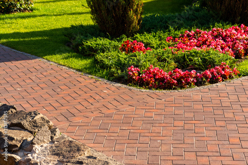 Fotografie, Obraz Path from red paving slab next to flowers in landscape design