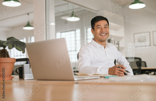 Fototapeta Smiling young Asian businessman working alone at his office desk