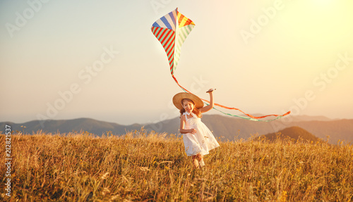Fotografie, Obraz  happy child girl running with kite at sunset outdoors