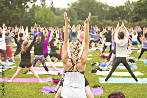 Foto  big group of adults attending a yoga class outside in park