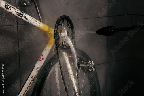Services professional washing of bicycle in the workshop. Close-up of hand Young Caucasian stylish man doing bicycle cleaning using an automatic electric water pump. Sprays scatter from the pressure.