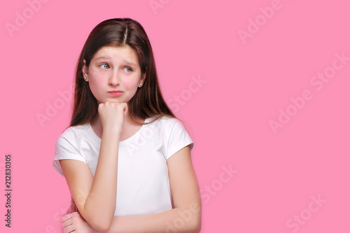 Fotomural  Teen girl against pink background with skeptic facial expression