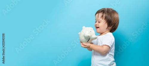Fototapeta Toddler boy with a piggy bank on a blue background obraz