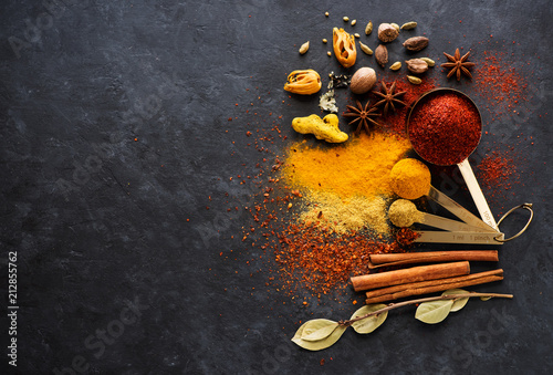 Photo  Selection spices, spicy and herbs in metal spoons, top view