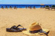 Straw hat and flip flop sandals on the golden sand at the tropical beach. Summer time concept.