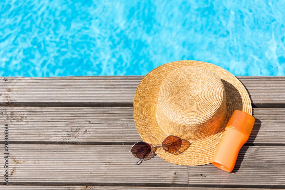 Fototapeta top view of wicker hat, sunglasses and sunscreen near swimming pool