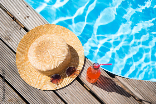 Photo top view of wicker hat, sunglasses and bottle with summer drink near swimming po