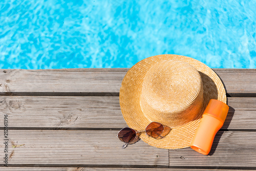 Photo top view of wicker hat, sunglasses and sunscreen near swimming pool