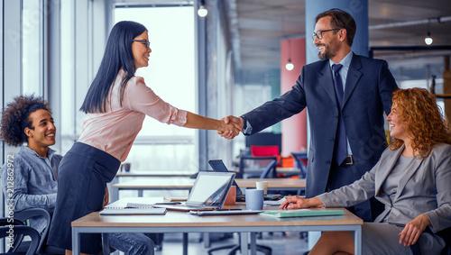 Fotografía  Two business teams successfully negotiating, shaking hands