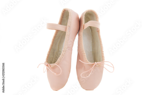 isolated pair of beginner ballerina shoes placed on tiptoes / pink baby shoes for learning to dance