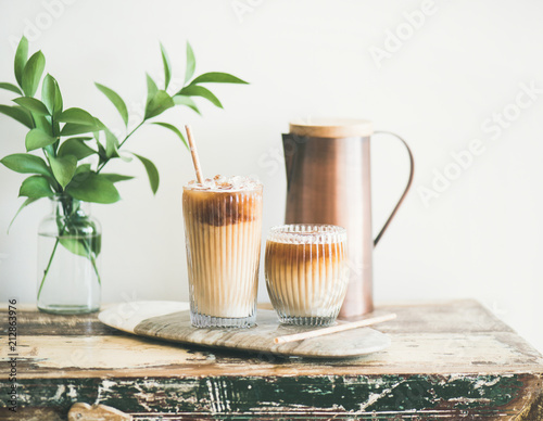 Iced coffee in glasses with milk and straws on board over rustic wooden table, white wall, jug and plant branch in vase at background, horizontal composition. Summer refreshing beverage