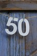 A paper cut number fifty pegged onto string across a wooden shed door painted a rustic, pastel blue , birthday card image