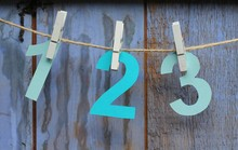 The Numbers One, Two And Three Cut From Shades Of Blue Paper , Pegged On String In Front Of A Painted Rustic Blue Shed Door , Rustic Paint Work.