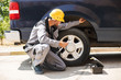 Young mechanic in work clothes and yellow hardhat using wrench for changing wheel outdoor