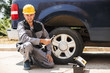 Smiling mechanic in work clothes and yellow hardhat happily looking in camera holding wrench for changing car wheel outdoor