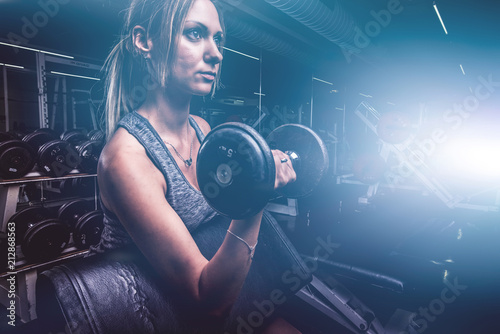Foto Young beautiful woman doing biceps curl with EZ curl bar in a gym