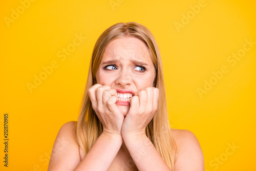 Fotografía Woman with nervous expressions face, keeps hands near mouth and stare with big eyes against yellow background