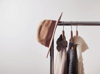 Knitted sweaters on hangers and felt hat