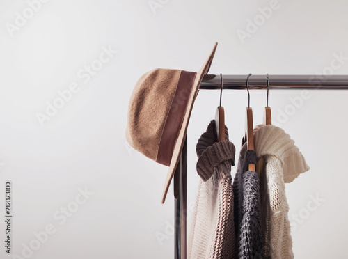 Knitted sweaters on hangers and felt hat - fototapety na wymiar