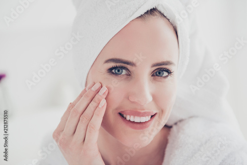 Fototapeta  Close up portrait of cute mature woman looking straight at camera smiling with her teeth wearing white bathrobe and turban