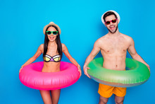 Happy Couple With Multi-colored Lifebuoys At The Waist Laughing Cheerfully And Looking At The Camera Standing Against On Blue Background