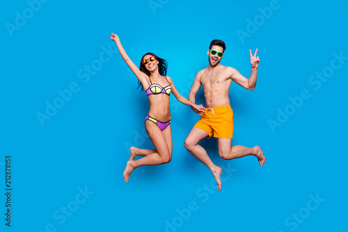 Obraz Full length portrait of a joyful young woman and happy man in eyewear, dressed in swimsuit, jumping and putting hands up and make v-sign over blue background with copy space for text - fototapety do salonu