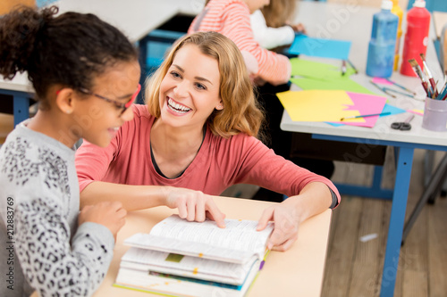teacher helping schoolgirl at school