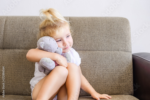 Portrait of emotional adorable toddler girl hugging her toy, teddy bear and sitting on the sofa, indoor in the light room. Devotion, child care concept. Selective focus, copy space.
