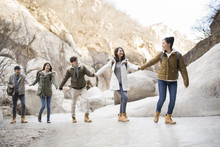 Happy Young Chinese Friends Holding Hands Enjoying Winter Outing