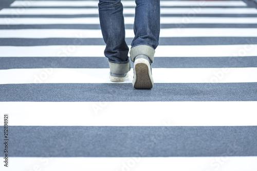Man wear jeans walk across the street on the crosswalk Wallpaper Mural