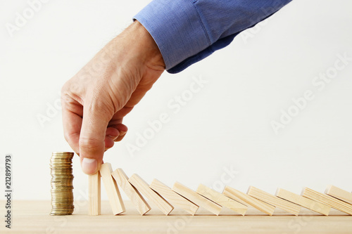Fototapeta concept image of investing and banking. man hands blocking the domino effect, saving a stack of coins. obraz