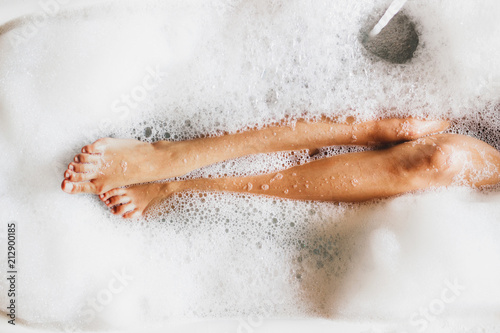 Foto Woman legs in bath foam