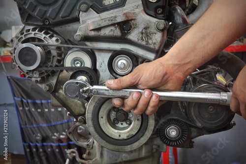 Photo Worker fixing pk belt, pulleys and alternator at modern car engine, closeup of h