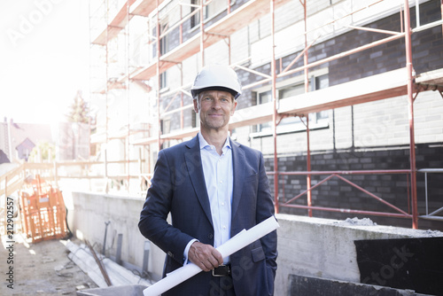 Portrait of confident architect wearing hard hat on construction site