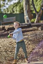 Boy In Garden Playing With Foam Baseball Bat And Ball