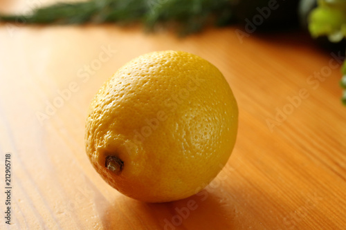 Single fresh ripe lemon on a wooden table in the kitchen