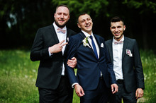Groomsmen And Groom Posing Outdoors On The Wedding Day.