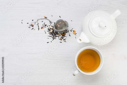 Fotografia, Obraz cup of tea with teapot and closed infuser with black tea on table