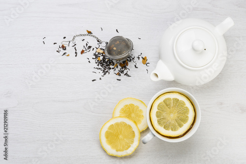 cup of tea with lemon slices, teapot and infuser on table Poster