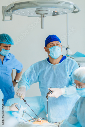 Fotomural  Surgeons team preforming operation uterus removal in hospital operating theater, male surgeon operating patient working with surgical laparoscopy instruments