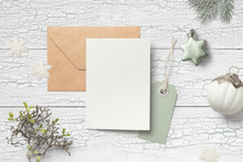 Minimalist Christmas Card Mock Up (portrait Format) With Green Fir Twigs, Baubles, Card, Envelope, Hangtag And Glitter Snowflakes On A White Wooden Background