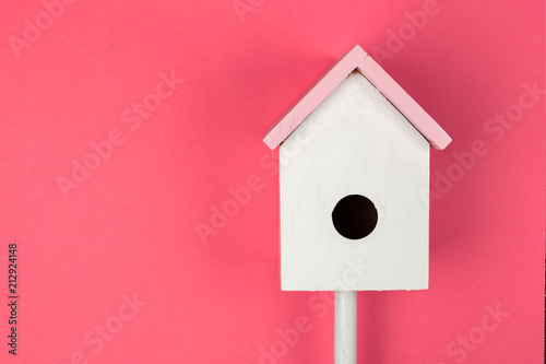 Tableau sur Toile Wooden birdhouse on pink background top view