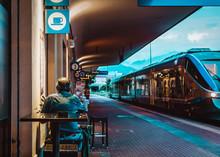 Senior Drinks Coffee On Train Station