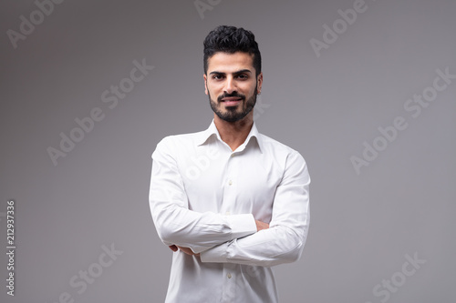 Photo  Young smiling bearded man with arms crossed