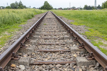 View Of Railway Tracks Approaching To Exterior Facade Of Auschwitz Birkenau Concentration Camp