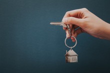 Woman's Hand Holding House Key With House Shape Key Chain.